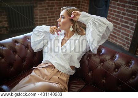 Luxury lifestyle. Glamorous middle-aged woman with enlarged full lips and evening makeup sitting on a leather sofa. High fashion shot.