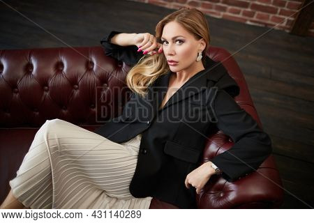 Portrait of a fashionable middle-aged woman with enlarged full lips sitting on a leather sofa. Cosmetology, plastic surgery, rejuvenation.