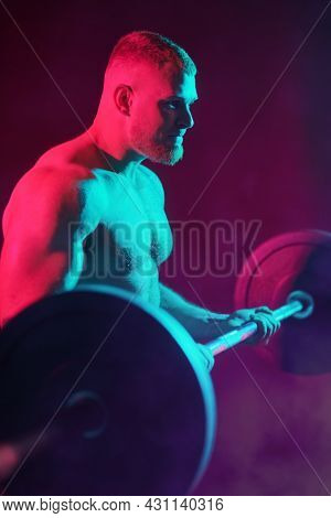 Weightlifting. A male weightlifter lifts the barbell with effort. Professional sports. Studio portrait in mixed colored light.
