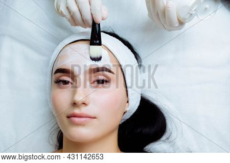 Facial Cosmetic Procedure In Spa Salon. The Procedure For Applying A Mask To The Face Of A Beautiful