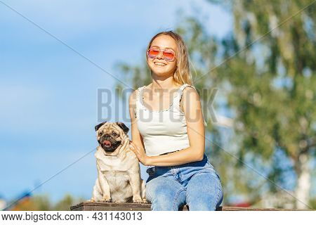 Stylish Young Girl In Sunny Glasses Goes For Walk With Doggy Pug In Park In Spring In Summer In Sunn