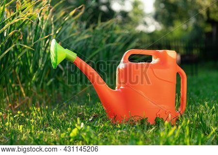 Orange Watering Can On The Green Grass In The Garden During Sunset
