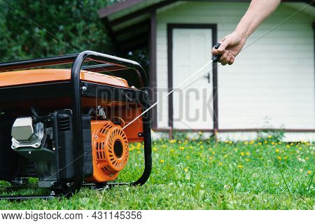 Hand Starts A Portable Electric Generator In Front Of A Summer House In Summer
