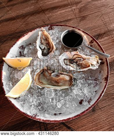 Fresh Open Oyster With Lemon On A Plate With Ice And Sauce On The Dark Kitchen Table. Seafood Appeti