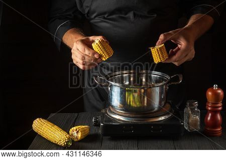 The Chef Cooks Corn. Close-up Of A Cook Is A Hand While Cooking In A Restaurant Kitchen. Free Advert