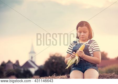 Adorable child having fun in a wheat field on a summer day, playing at hay bale field during harvest time.