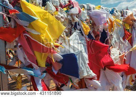Multicolored fabric rags flags in Buddhist temple and pilgrimage site Ruwanweliseya Dagoba. Anuradhapura, Sri Lanka
