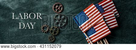 some cogwheels, some small flags of the Uniteds States of America and the text labor day on a dark gray background, in a panoramic format to use as web banner or header