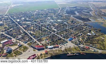 Top View Of The Small Town. Aerial Shot Of A Small Old Town By The River With Tileed Roofs. Neighbor
