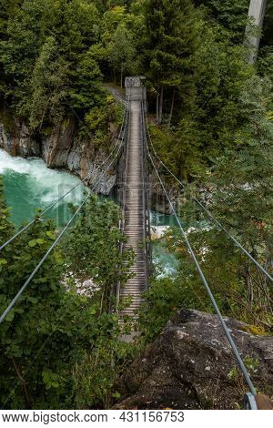 Suspension bridge over the Reuss river with rapids at Gurtnell in German-speaking Switzerland. Cloudy day, copy space. Nobody inside