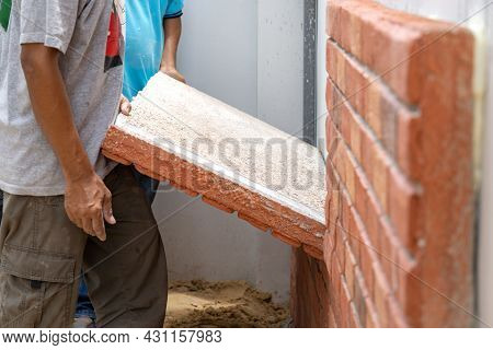 Thai Labour Are Installed Foam Brick Board On The Cement Wall