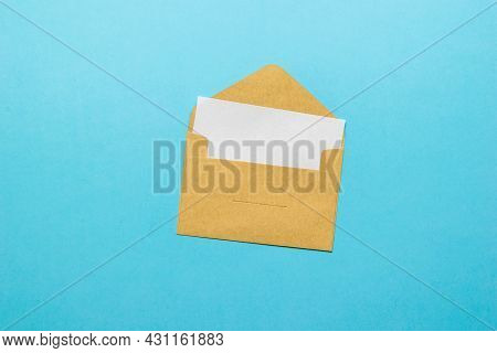 An Open Postal Envelope With An Enclosed White Sheet On A Blue Background. The Concept Of Mail Corre