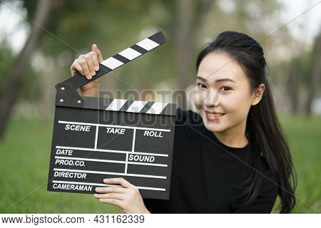 Asian Woman Holding Movie Clapper Board In Her Hands, Entertainment Film Concept