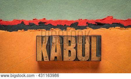 Kabul word abstract in vintage letterpress wood type printing blocks against abstract paper desert landscape in red, orange and black tones
