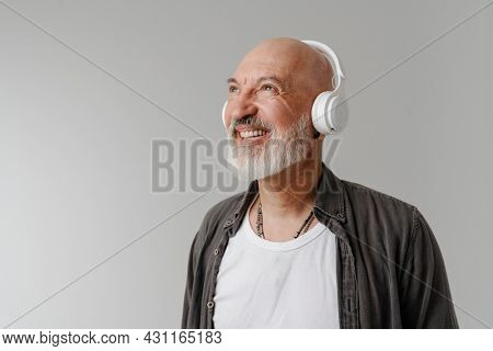 Bald bearded european man listening music with headphones isolated over white background