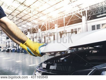 Technician Hand Pulling Up Car Hood For Maintenance In The Repair Garage