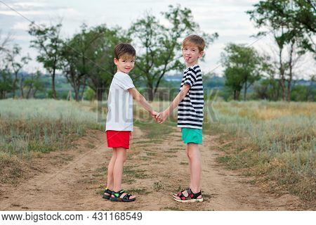 Two Brothers Holding Hands, Turning Around And Looking At Camera. Older Brother Shows Tongue. Funny