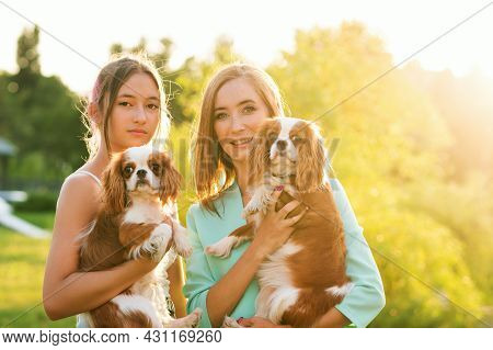 Horizontal Authentic Portrait Of Breeder. Mother And Daughter Walking At Sunset On Summer Day With P