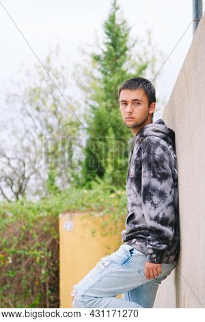 Teenager Sitting On Fence Wearing Sweatshirt And Jeans