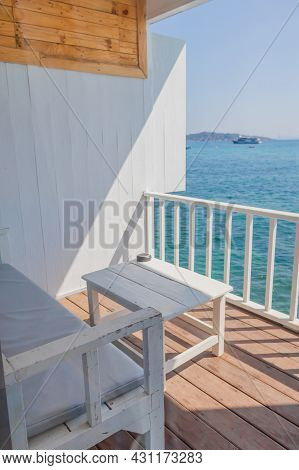 A View Of The Resort's Balcony Overlooking The Sea, Where The Terrace Features Wooden Sofas And Whit