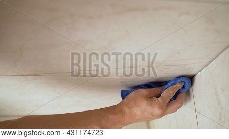 Male Hands Wipe The Dust After Grouting Ceramic Tiles With A Rag. A Worker Wipes The Tiles With A Ra