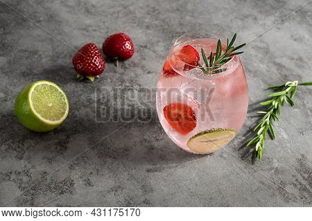 Premium Pink Gin With Strawberry, Lime, And Rosemary. Refreshing Alcohol Cocktail With Ice.
