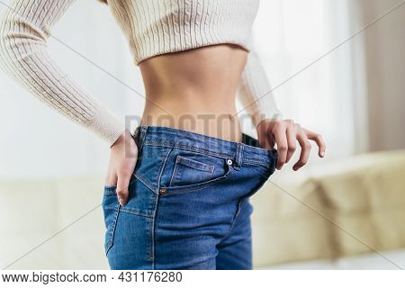 The Girl Holds Jeans In Her Hand, Shows A Thin Waist Slim Female Body In Large Jeans. Diet Concept.