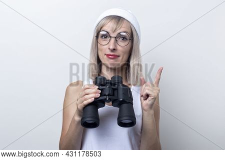 Friendly Young Woman Holding Binoculars Pointing With Her Finger On A Light Background
