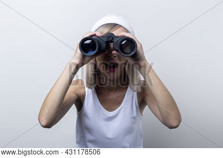 Surprised Young Woman Looking Through Binoculars On A Light Background