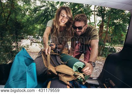 Young Couple Unpacking Camping Equipment Sleeping Bag And Mat.