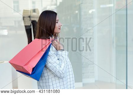 Tired Brunette Holding Shopping Bags On Showcase Background. Black Friday. Exhausting Shopping.