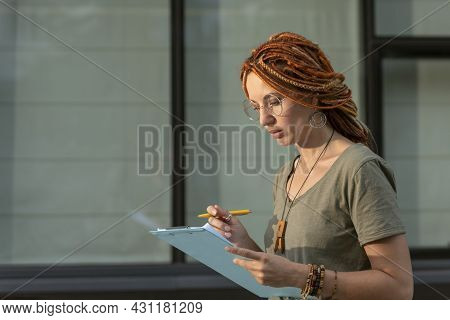 Young Girl Of Non-standard Appearance Reads Information On A Tablet. Student Conducts A Social Surve