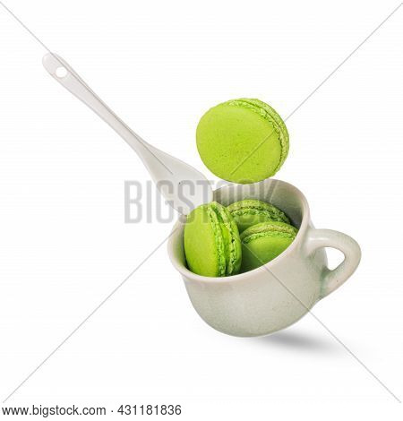 A Piece Of Green Pistachio Macaroon Or French Macarons Falling On A Soft Green Ceramic Cup Filled Wi