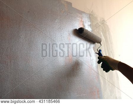 Hand In A Roller Glove Painting A Textured Shiny Wall, A Snippet Of An Off-screen Painter's Workflow
