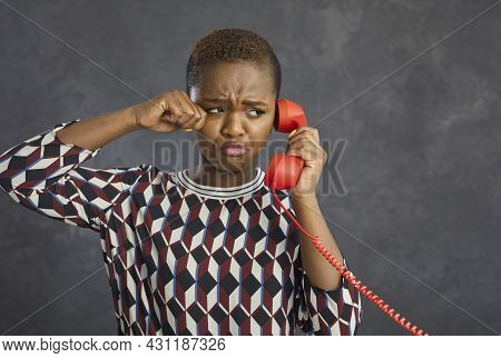 Portrait Of Unhappy Capricious African American Woman Crying While Talking On Landline Retro Phone.