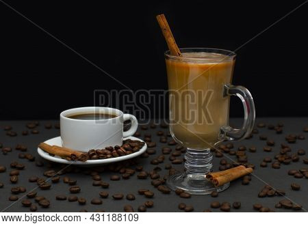 A Cup Of Hot Coffee In A White Coffee Cup. A Cup On A Saucer With Roasted Coffee Beans And Cinnamon