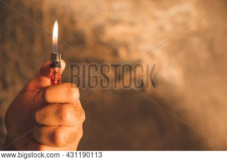 Close Up Hand Man With Lighters Kindle The Fire On Burning Background.