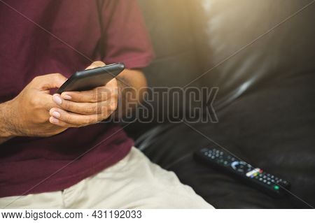 Young Man Holding Smartphone And Television Remote Control. Hands Pointing To Tv Set And Turning It