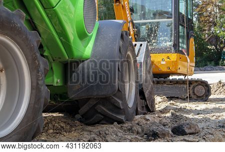 Two Small Excavators On A Large Construction Site. Bright Green On Wheels And Yellow On Tracks. Eart