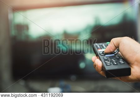 Young Man Holding Television Remote Control. Hands Pointing To Tv Screen Set And Turning It On Or Of