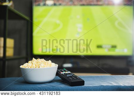 Popcorn And Television Remote Control On Football Program Tv Screen Background. Watching Tv Relax Co