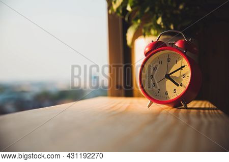 Alarm Clock On Wooden In The Morning With Sunlight.