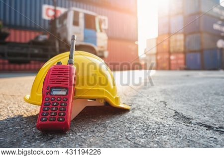 Radio Walkie Talkie And Helmet Hard Hat On The Floor At Container Cargo Harbor With Sunlight Backgro