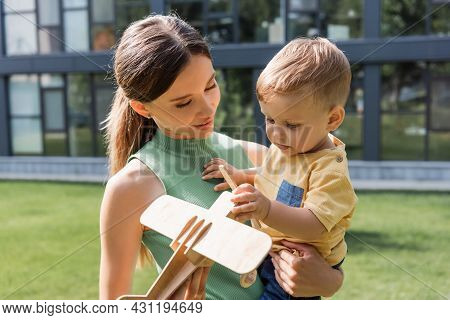 Smiling Mother Holding Toy Wooden Biplane Near Toddler Son