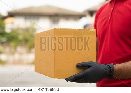 Postman In Red Uniform Holding Package Delivery At Home