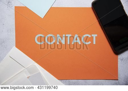 Contact Text On Orange And Baby Blue Background Flat Lay Concept. Suitable To Used As Title Cover Ea