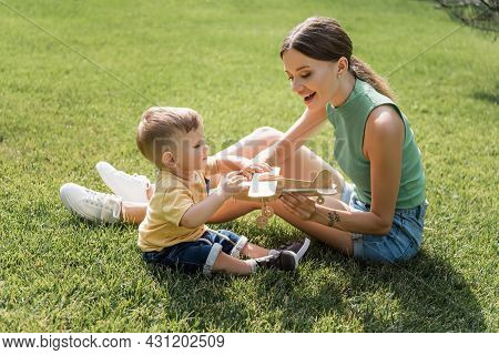 Cheerful Mother Holding Toy Biplane Near Toddler Son On Grass