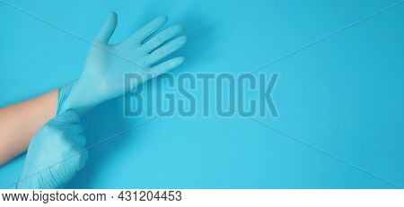 Hand Is Pulling Blue Latex Gloves On Blue Background.