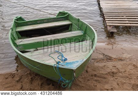 A Shabby Wooden Boat Painted Green With Two Benches For Rowing Moored By A Rope At A Small Board Pie