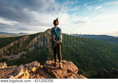 A Young Tourist Girl With A Backpack Enjoys The Sunset From The Top Of The Mountain. A Traveler On T